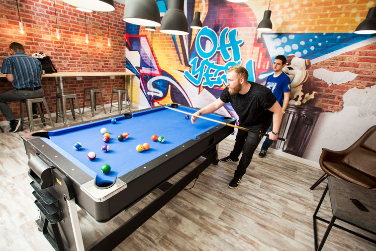 DLG colleagues playing snooker with graffiti-style wall art