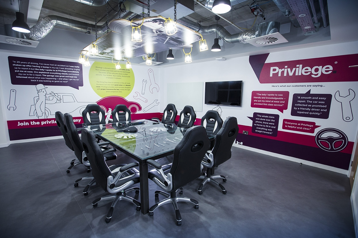 Meeting room with Privilege-themed wall art and bucket-style car seats around a table