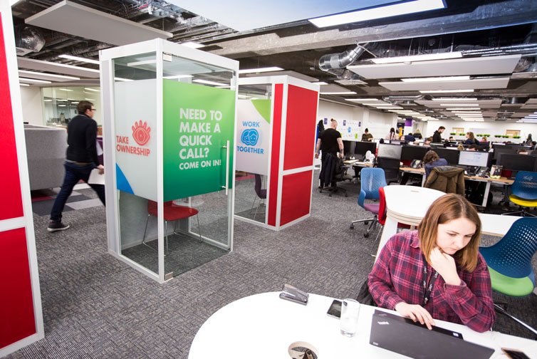 DLG colleagues working in open-plan office featuring two phone box-style glass privacy booths