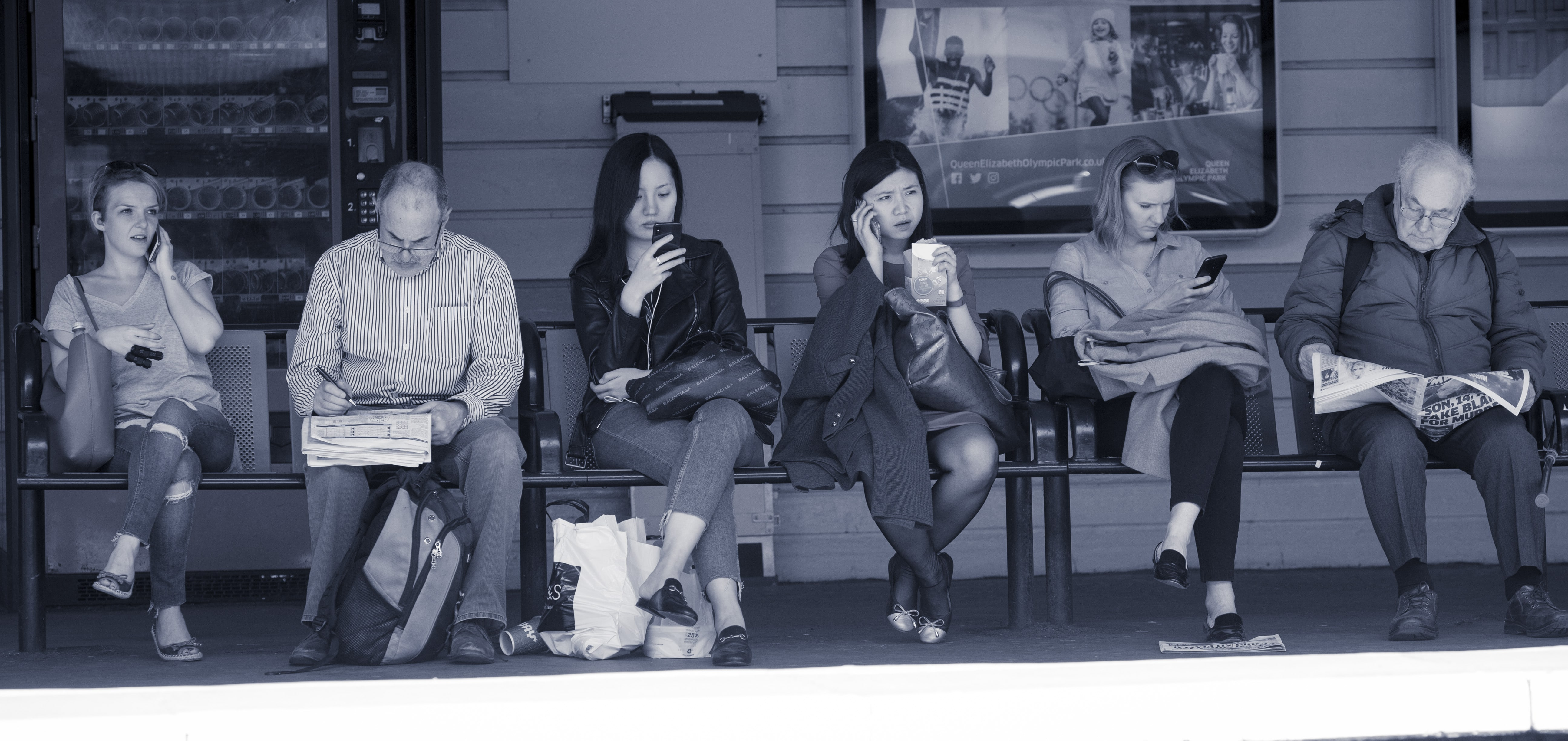 Passengers sitting in a row on a station platform, texting or reading newspapers