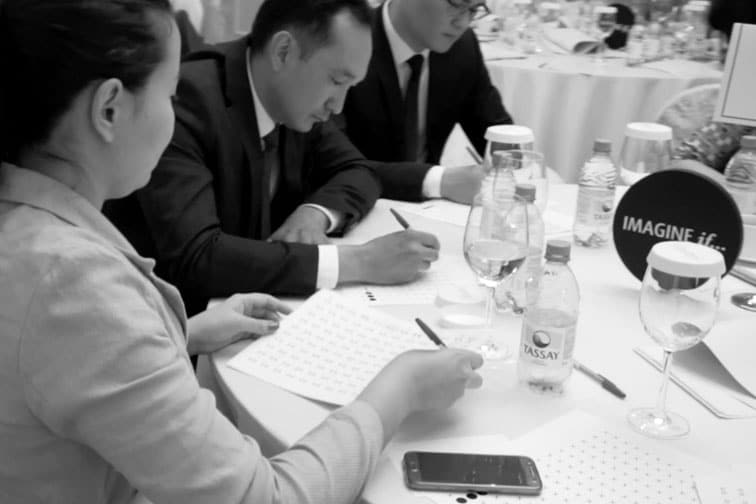 Three Air Astana colleagues concentrating while writing