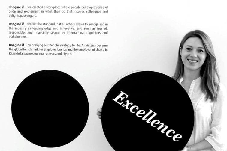 Air Astana's Imagine if... campaign with colleague holding black disc inscribed with the word Excellence