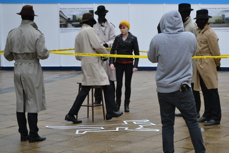 Five actors dressed in Macs, trilbies and balaclavas, with chalk figure drawn on the floor