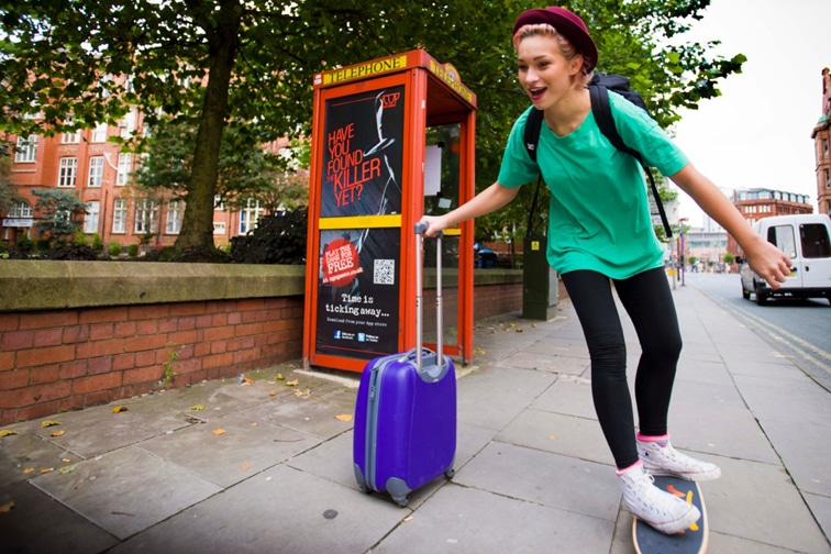 Girl skateboarding past a telephone booth advertising iCop