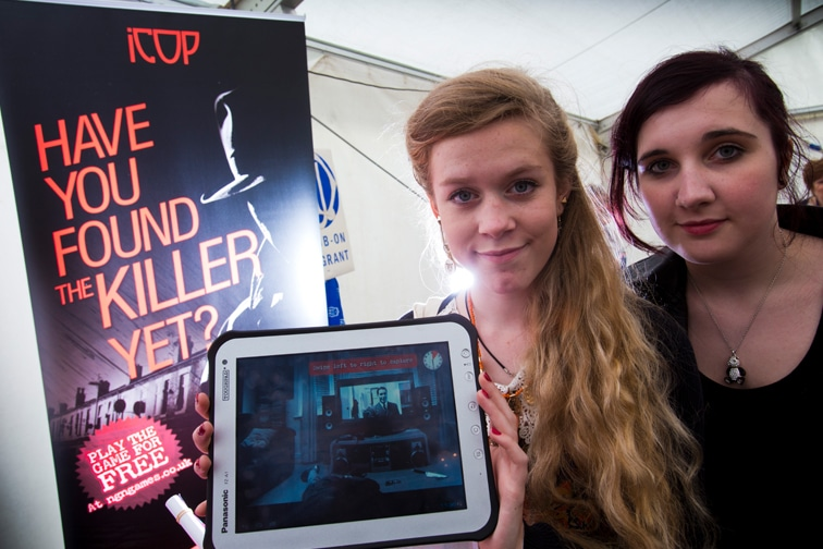 Two girls playing the iCop game on a tablet