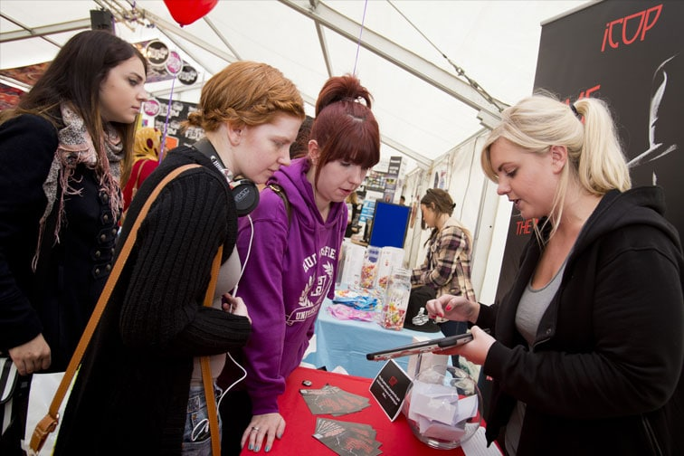 Three girls at an iCop stall in a marquee concentrating as the game is explained