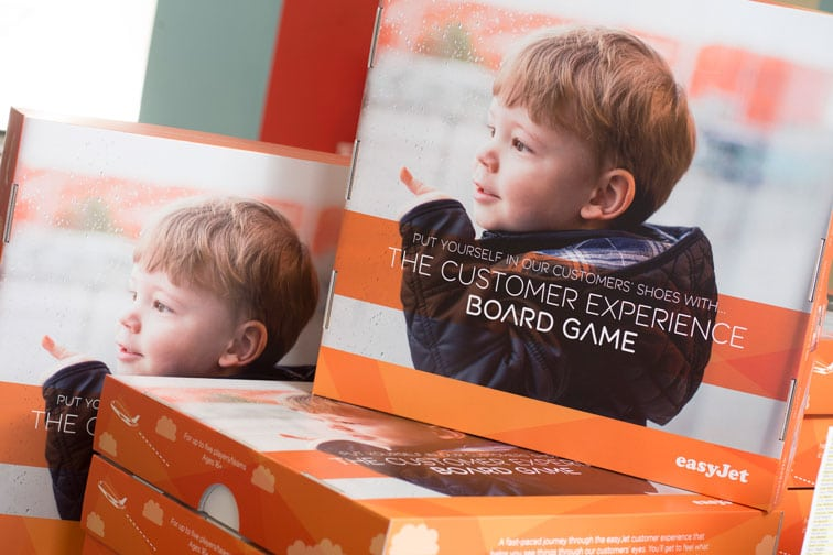 Customer Experience Board Game boxes with smiling toddler on the cover